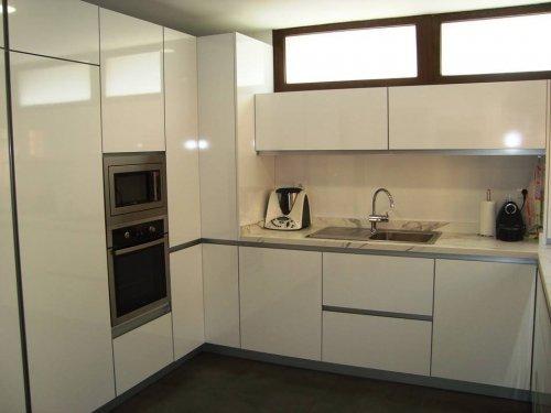 Cocina de formica blanco brillo con canto de mismo color, tiene tiradores integrados en el casco (gola),fregadero sobreencimera y zocalo de alumino, también tienen muebles bajos de mayor altura para mayor capacidad.