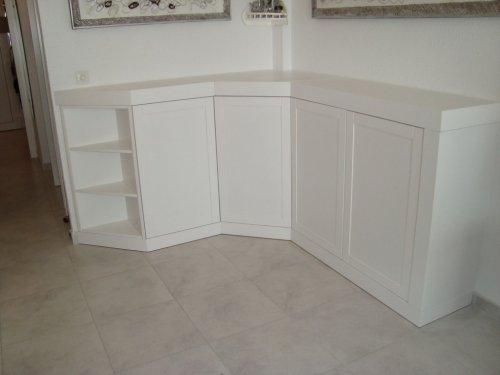 Mueble de salón a medida lacado en blanco, incluye tapa y pie de 9cm de grueso, estantería vista a 45 grados a la vista, y mueble rincon de chaflán.