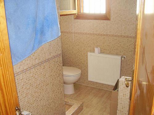 Reforma integral de un cuarto de baño, en tonos marrones, con mampara y plato de ducha de obra.