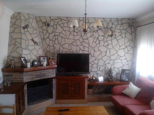 Salon con pared de piedra y chimenea