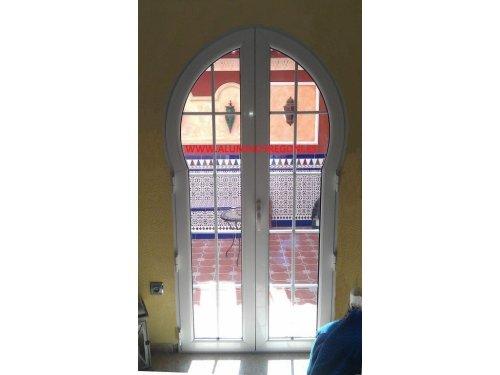 Puerta de aluminio lacado blanco de 2 hojas abatibles con arco árabe, doble acristalamiento Climalit 4/8/4 incoloro con palillería fresada