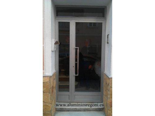 Puerta de hierro de 2 hojas abatibles y paño fijo superior con cristal laminado